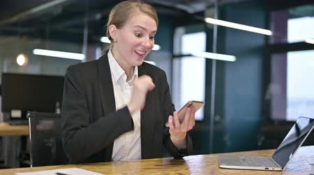 só as mulheres jovens : Young Businesswoman Celebrating Success on Smartphone in Office