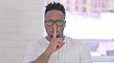 one man only : Portrait of Casual African Man Putting Finger on Lips Stock Footage