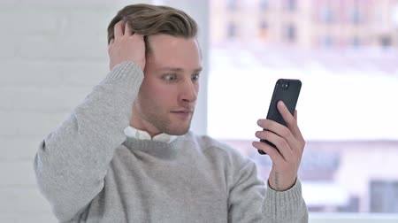 distraught : Portrait of Sad Creative Young Man reacting to Loss on Smartphone