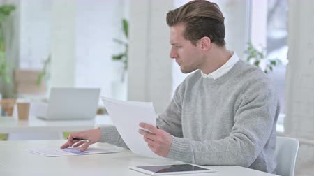 freelance work : Creative Young Man checking Financial Documents, Reading