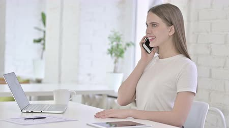 negotiate : Happy Young Woman Talking on Smart Phone in Office Stock Footage