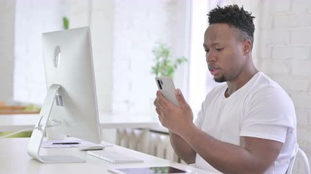 página da internet : Focused Casual African Man using Smartphone in Modern Office