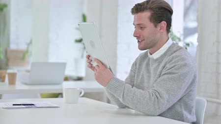 answering : Creative Young Man doing Video Chat on Tablet in Office