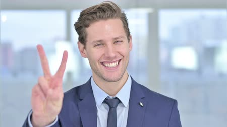 primer lugar : Portrait of Successful Young Businessman showing Victory Sign