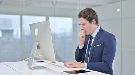 coughing : Sick Young Businessman Working on Desk Top and Coughing in Office Stock Footage