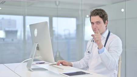 merging : Cheerful Young Male Doctor Pointing Finger at Camera