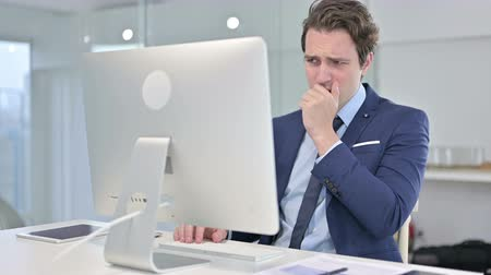 симптом : Young Businessman Working on Desk Top and Coughing