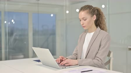 só as mulheres jovens : Ambitious Young Businesswoman Working on Laptop in Office