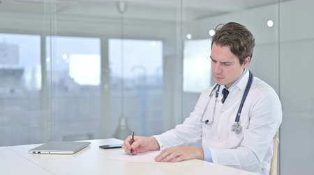 adults only : Serious Young Doctor doing Paperwork in Modern Office