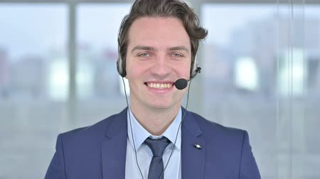 whispering : Portrait of Young Businessman wearing Microphone and Smiling Stock Footage