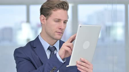 página da internet : Portrait of Serious Young Businessman using Tablet