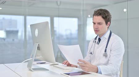 banking document : Serious Young Doctor doing Paperwork on Desk Top in Office