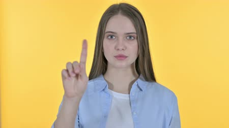 elválasztás : Casual Young Woman saying No with Finger Sign, Yellow Background