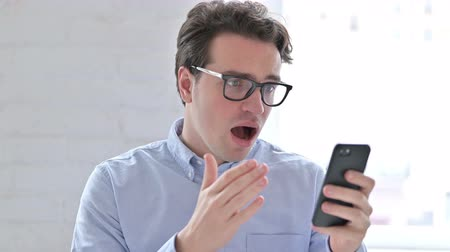 one man only : Portrait of Young Man reacting to Failure on Smartphone Stock Footage