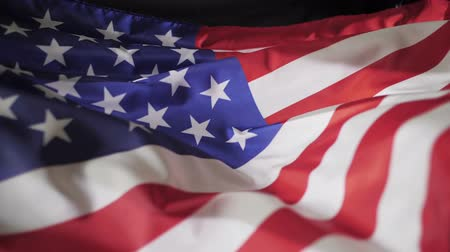 июль : Flag of America in the wind on black background, slow motion