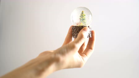 snow globe : Hand hold Christmas snow globe on white background Stock Footage