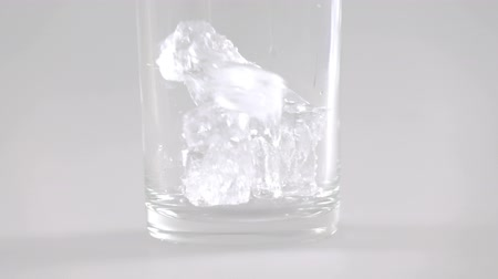 mrazák : Close up of ice cubes falling into glass slow motion