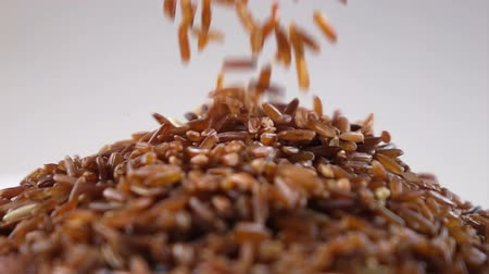 brown rice : Brown rice pouring on stack slow motion