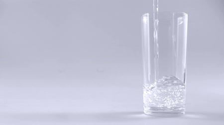 karbonatlı : Pouring water in glass on white background slow motion Stok Video