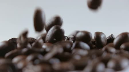 grained : Coffee beans falling on white background