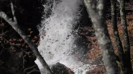 наводнение : Waterfall splashing on rock in forest