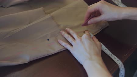 Seamstress marks a pattern on beige fabric.