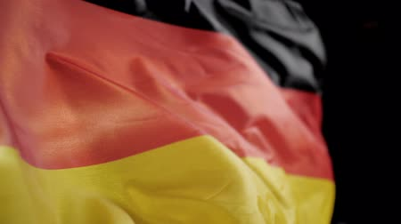 národnost : German flag on black background slow motion.