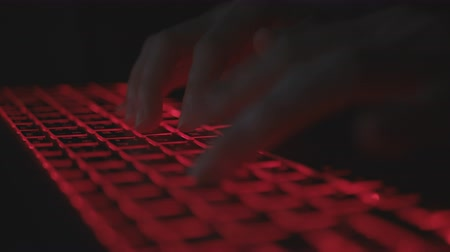 Programmer typing code on laptop at night.