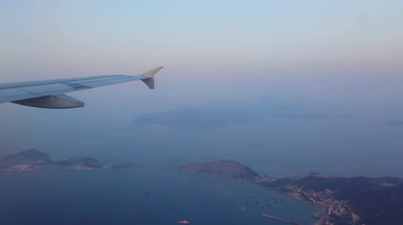ozón : Wing of airplane flying over islands and sea.