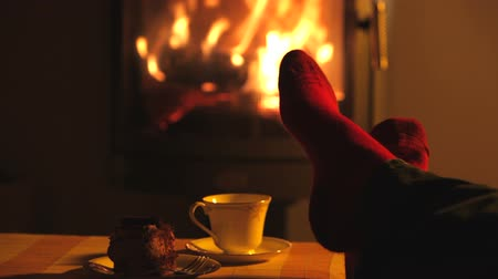 xícara de café : Man relaxes by warm fire and wriggles his toes.