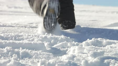 deep snow : Close up of man in boots walking through crisp snow. Stock Footage