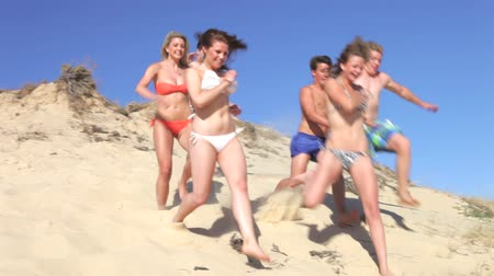 tizenéves lányok : Group of teenage friends standing at the top of dune before running down and past camera.