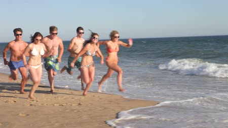 ifjú : Group of teenagers run at speed through surf along beach.