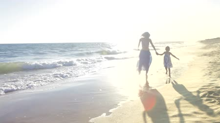 smích : Little girl holds mothers hand as they skip through the surf and then past camera.