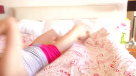 cama : Woman rolls into frame on bed before looking into camera and smiling.