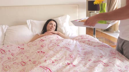 sheet : Man walks into bedroom and places tray with breakfast in front of woman in bed. Stock Footage