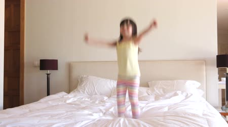 noční prádlo : Young girl bounces excitedly on bed looking at camera.