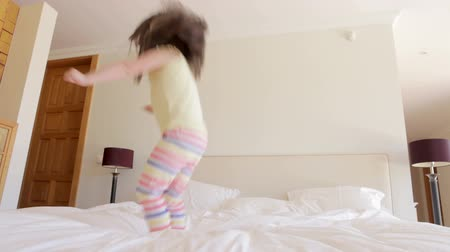 noční prádlo : Young girl bounces excitedly on bed before sitting down looking at camera.