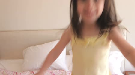 noční prádlo : Young girl runs into bedroom and climbs onto bed before bouncing up and down. Dostupné videozáznamy