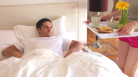 сюрприз : Woman walks into bedroom and places tray with breakfast in front of man in bed.