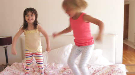 sheet : Two young girls bouncing excitedly on bed looking at camera.