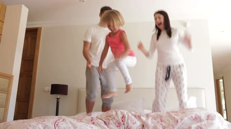 izgatott : Young girl bounces excitedly on bed with parents. Stock mozgókép