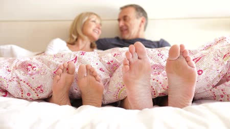 noční prádlo : Close up of feet wriggling as senior couple sit up and chat in bed.