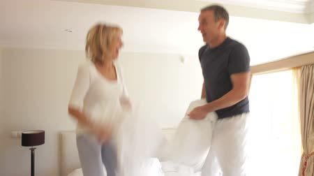 poduszka : Senior husband and wife bouncing on bed having pillow fight together.