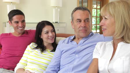 senior lifestyle : Happy couples relaxing on sofa chatting together. Stock Footage