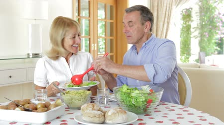 man eating : Senior couple seated around dining table serving one another. Stock Footage