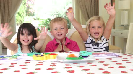 smích : Group of three children sit around table painting with fingers and showing messy hand to camera. Dostupné videozáznamy