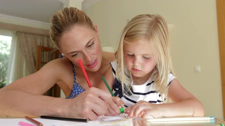 Картинки : Mother and daughter sitting at table working on picture with pens together. Стоковые видеозаписи