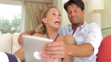 estilo de vida : Angry woman holds digital tablet and points to the screen before man snatches it from her.