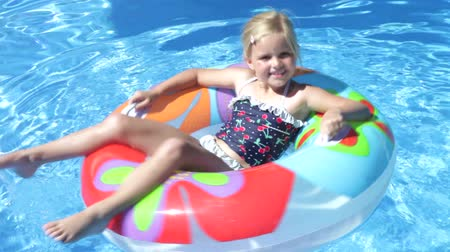 halkalar : Girl lying on inflatable rubber ring floating in swimming pool and revolving.